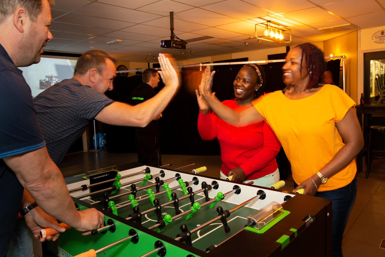 De dames Anna Namuddu (links) en Aisha Kulubyu spelen tegen Johnny Thys en Dennie Ballering.