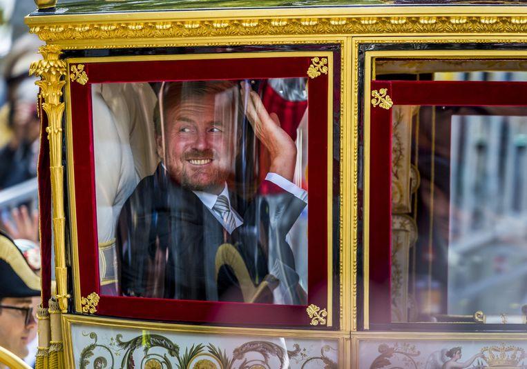 Koning Willem-Alexander zwaait vanuit de Glazen Koets onderweg van de Ridderzaal naar paleis Noordeinde op Prinsjesdag.   Beeld ANP