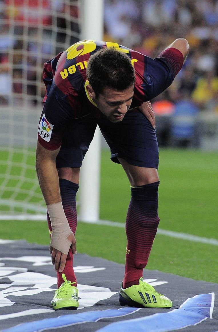 Alba grijpt naar zijn been in het duel tegen Sevilla Beeld afp
