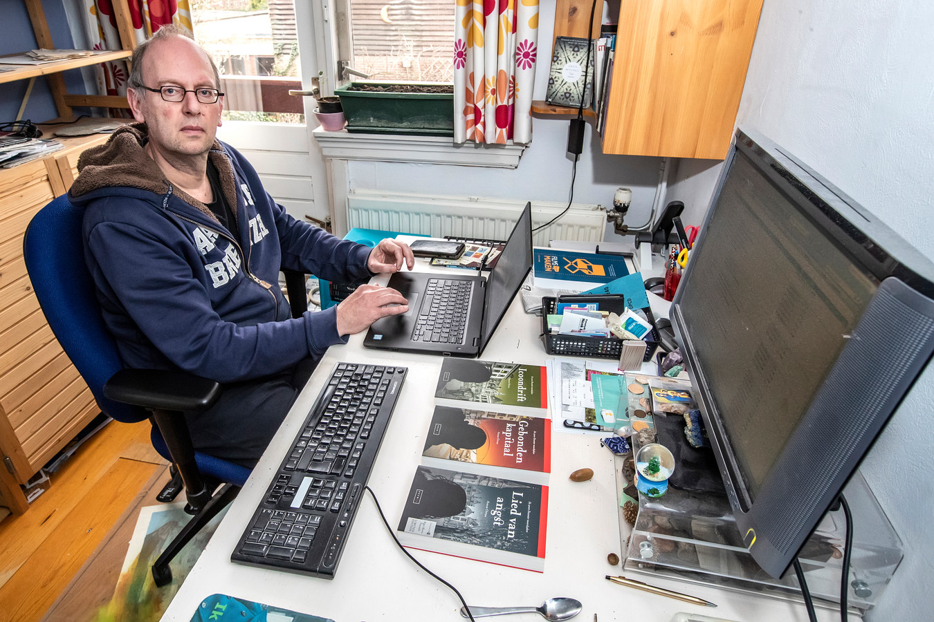 Almar Otten in zijn werkkamer thuis in Deventer. De computers zijn voorlopig gericht op de gemeentelijke websites.