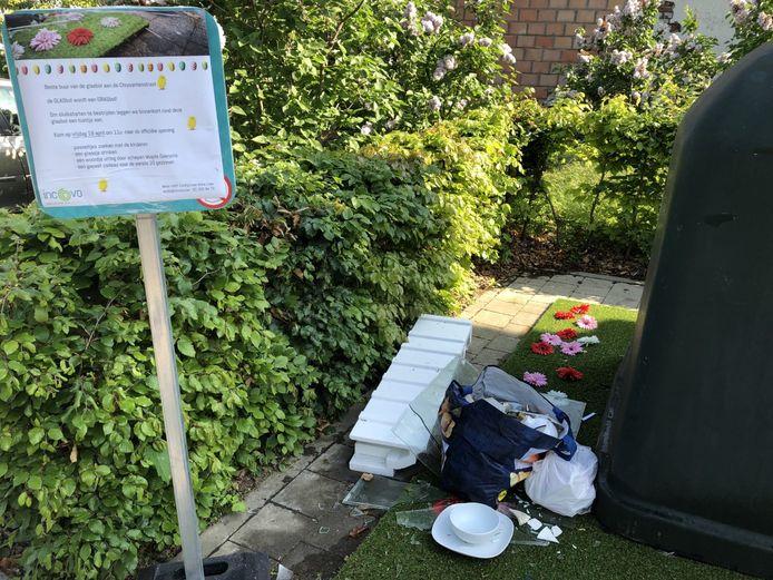 Het afval werd net naast het bordje met uitleg over het doel van het bloemenperkje achtergelaten.