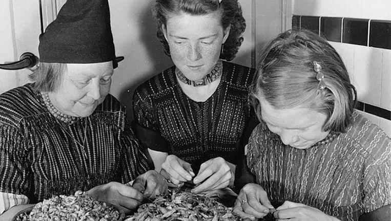 Volendamse vrouwen pellen in 1959 thuis, zoals vele dorpsbewoners, garnalen voor Klaas Puul. Beeld -