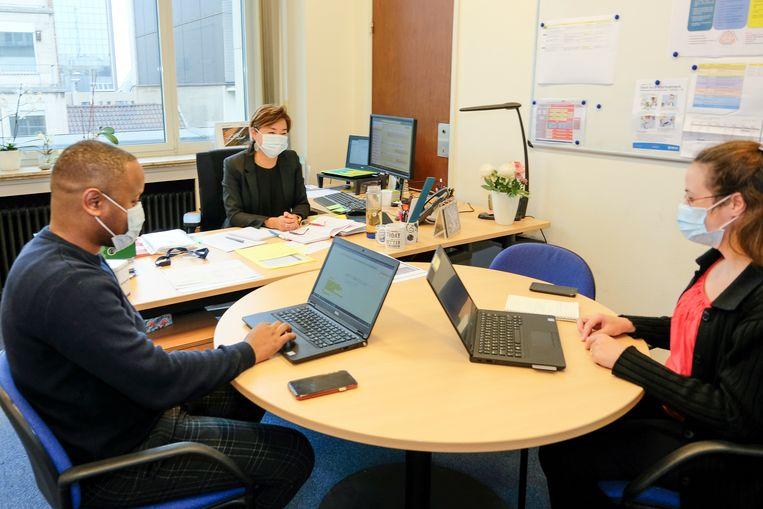Bij Total draagt het kantoorpersoneel een mondmasker waar geen 1,5 meter afstand kan worden bewaard, zoals hier tijdens een overleg. Beeld Marc Baert