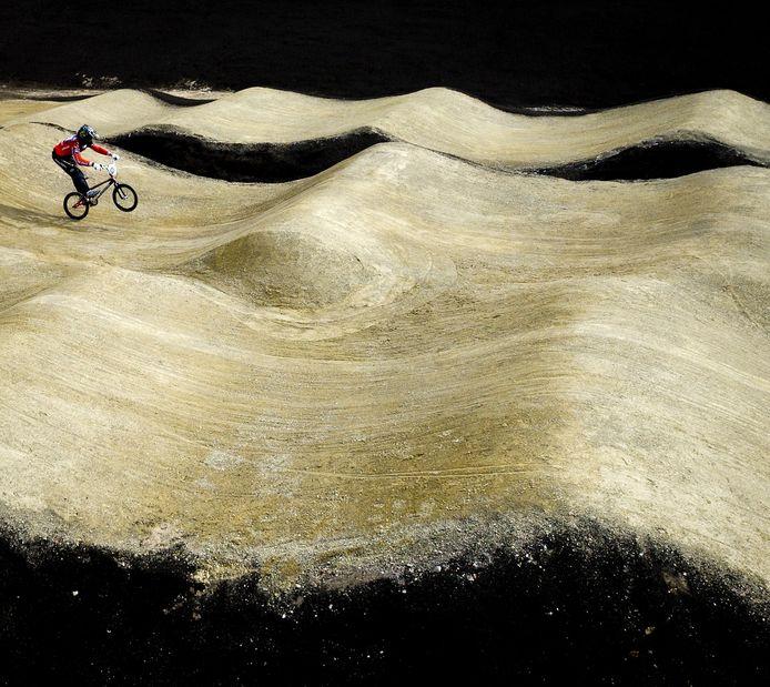 Een fietscrosser op de baan op Papendal.
