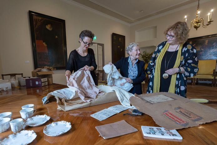 Junior conservator Mariëlle van de Kerkhof van Museum Helmond (links) kijkt wat Elisabeth de Jong van Beek en Donk en haar nichtje Emilie Lindenbergh (rechts) hebben meegebracht voor de expositie over de Helmondse jonkvrouw Emelie Wesselman.