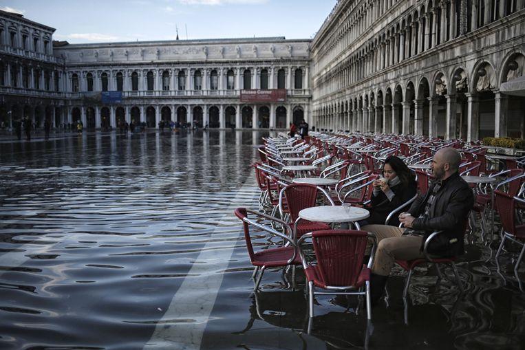 Toeristen op een overstroomd San Marcoplein in Venetië. Beeld AFP