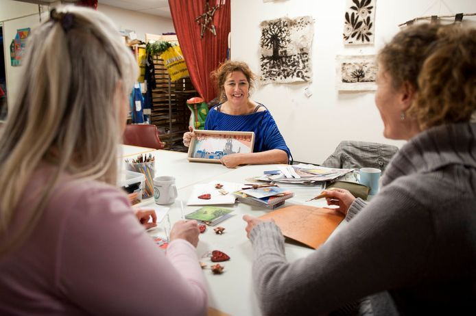 Dagbesteding ArtoMondo in Deventer is een van de twintig kleine zorgaanbieders die de alarmbel luidden. Ze vrezen dat ze door de verlaging van de tarieven in de gemeenten Deventer en Olst-Wijhe de dagbestedingsactiviteiten niet te kunnen voortzetten. Op de foto geeft Marianne de Bakker uitleg  over een kunstproject waar de dames van de dagbesteding mee bezig zijn.