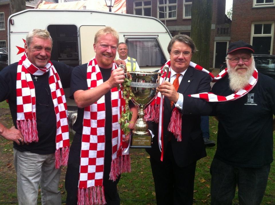 Martin Ostendorf (tweede van links) viert samen met commissaris van de koning Wim van de Donk en medewerkers de overwinning.