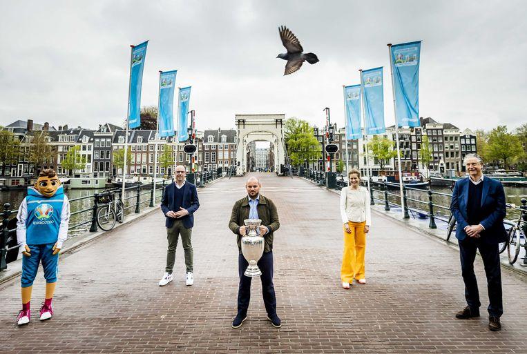 Toernooidirecteur Gijs de Jong (linksachter), ambassadeur Wesley Sneijder (m), wethouder Simone Kukenheim  en ArenA-directeur Henk Markerink (r) onthalen op 14 mei dit jaar de officiële beker van het EK voetbal op de Magere Brug in Amsterdam. De beker maakte een toer langs alle elf speelsteden.  Beeld ANP