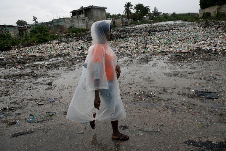 Een vrouw loopt langs een rivier in Port-au-Prince. Beeld REUTERS