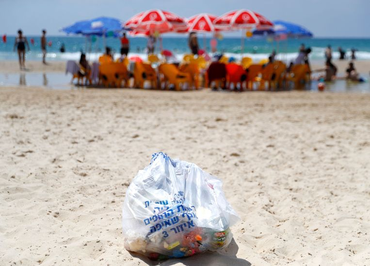 Een zak plastic afval op het strand in Israël.  Beeld AFP
