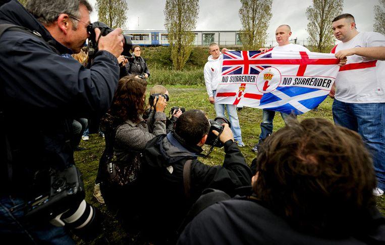 Leden van de English Defence League tonen zaterdag een vlag aan de media. Foto © Koen van Weel/anp Beeld