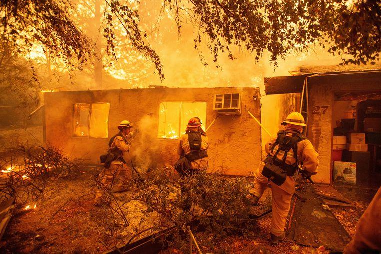 Brandweerlieden blussen een huis in Paradise. Beeld AFP