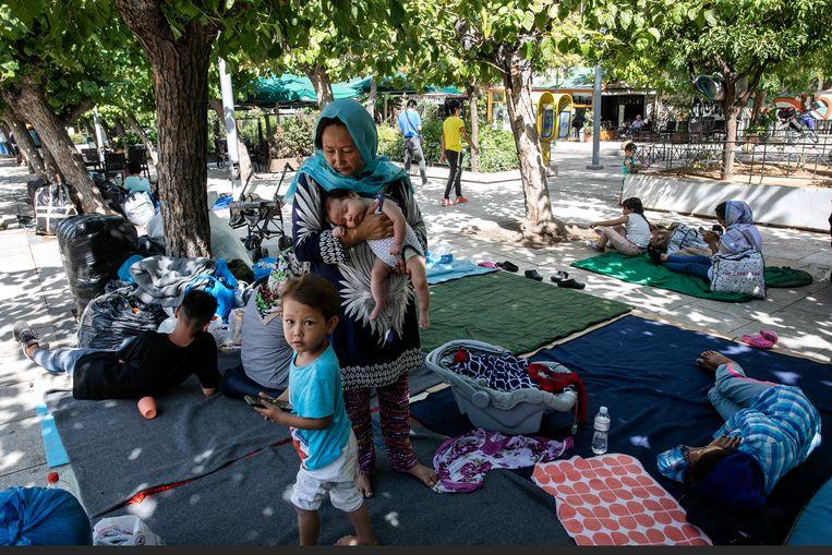 Migranten in een park in Athene. Als zij eenmaal een verblijfsstatus hebben, zijn hun levensomstandigheden in Griekenland vaak nog steeds niet goed.  Beeld AP