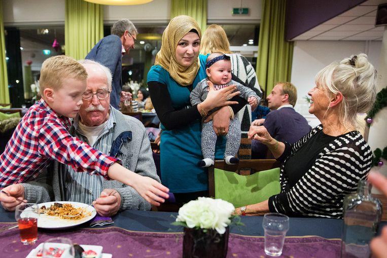 Nieuwe inwoners van Cromstrijen, vluchtelingen uit Syrië en Eritrea, koken op 17 december voor hun dorpsgenoten. Beeld Arie Kievit / de Volkskrant