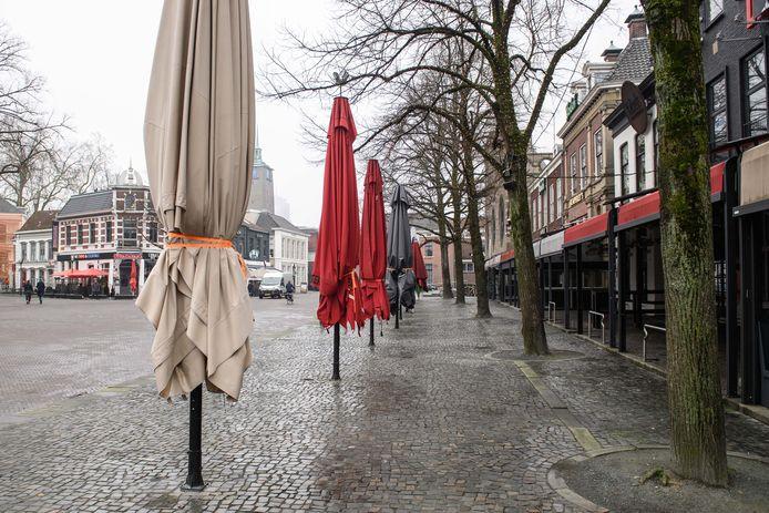 Parasols bij de horeca op de Oude Markt zijn dag en nacht ingeklapt, de terrassen zijn leeg.