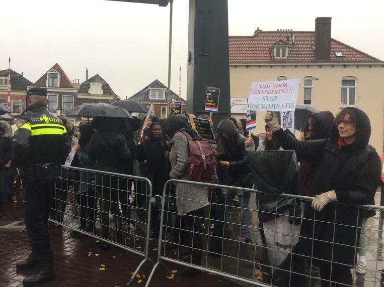 De demonstranten staan in Weesp achter een hek Beeld Malika Sevil
