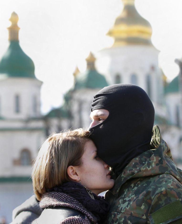 Een vrijwilliger van het Oekraïense Azov-bataljon neemt afscheid van zijn geliefde.