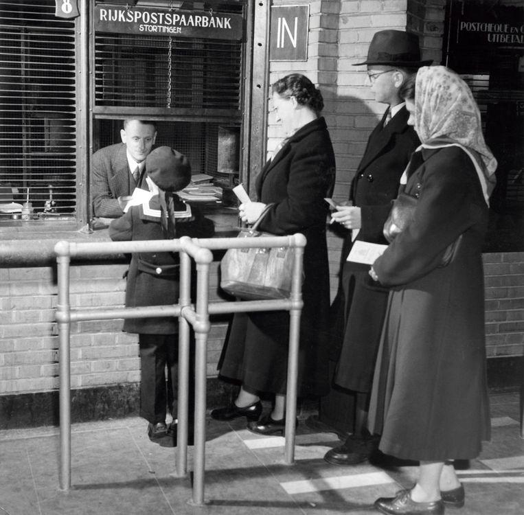Mensen staan in de rij voor het loket Stortingen van de Rijkspostspaarbank, Haarlem, 22 maart 1951. Beeld Hollandse Hoogte / Spaarnestad Photo