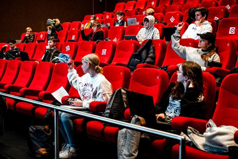 Vanwege ruimtegebrek in het schoolgebouw krijgen leerlingen van De Nieuwe School in Tilburg op anderhalve meter les in de Pathe bioscoop. Beeld Rob Engelaar