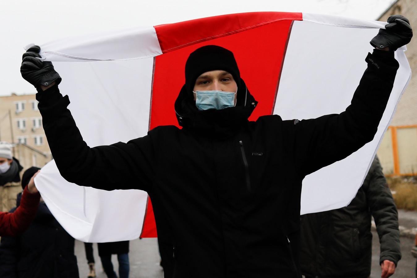 Een demonstrant in Minsk zwaait met een oude Wit-Russische nationale vlag tijdens een oppositiebijeenkomst om te protesteren tegen de benoeming van Loekasjenko na de presidentsverkiezingen.