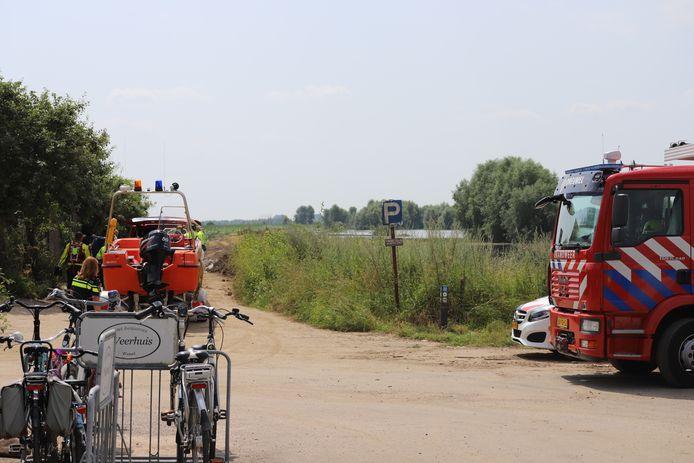 Hulpdiensten bij de Veerweg in Wamel. Zij zoeken naar een mogelijk lichaam in de Waal.