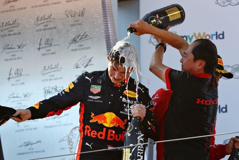 Max Verstappen viert zijn overwinning in de GP van Oostenrijk met Toyoharu Tanabe van Honda in 2019.  Beeld Getty Images