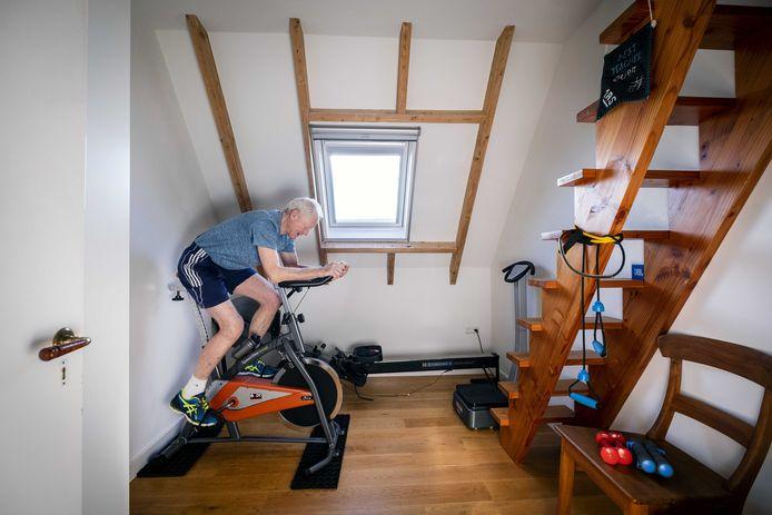 Een oudere man sport in zijn zolderkamer nu de sportscholen gesloten zijn vanwege het coronavirus.
