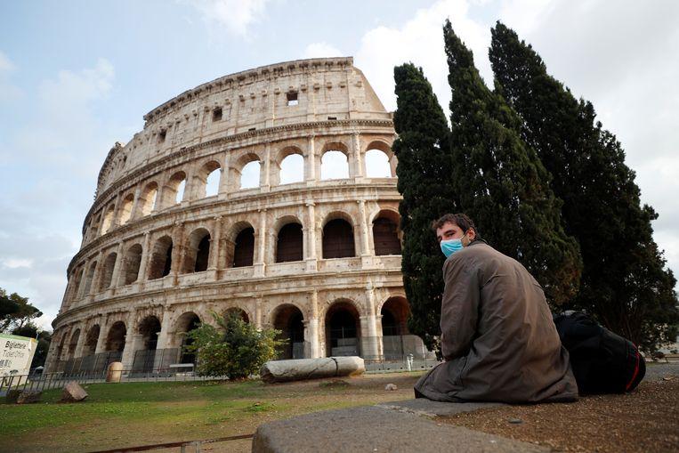 Een man met mondmasker aan het Colosseum in Rome. Beeld REUTERS