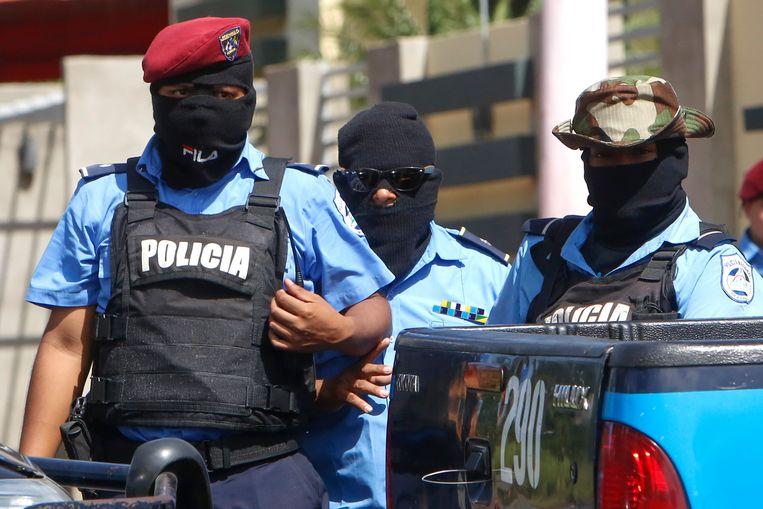 Gemaskerde politieagenten bij een wegafsluiting in de Nicaraguaanse hoofdstad Managua  waar betogers de vrijlating eisten van de studenten die vastzaten in de kerk. Beeld AP