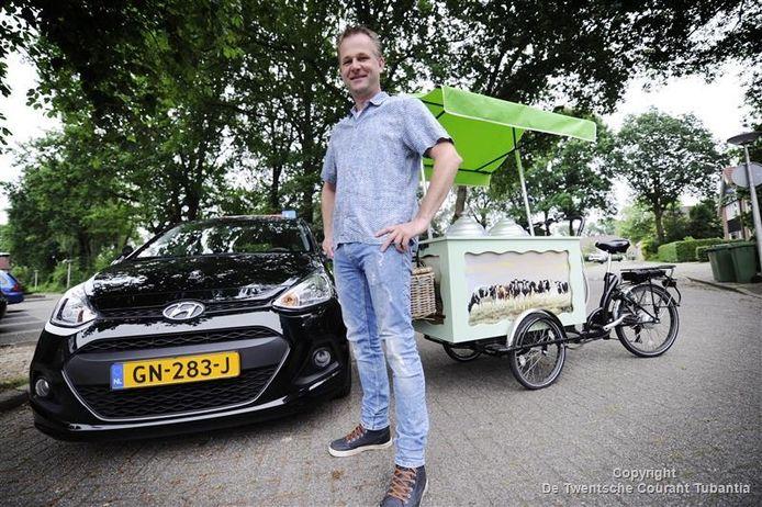 Jeroen Sanderman tussen zijn lesauto en de ijscokar.