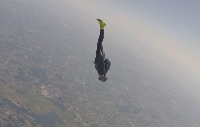Met gestrekte benen, de armen tegen het lichaam gedrukt en het hoofd naar beneden duikt Luc Maisin uit het vliegtuig.