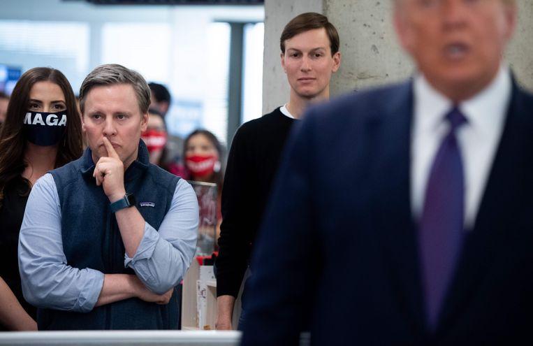 Campagneleider Bill Stepien (l) en adviseur-schoonzoon Jared Kushner (R) luisteren naar een mededeling van Trump op verkiezingsdag. Beeld AFP