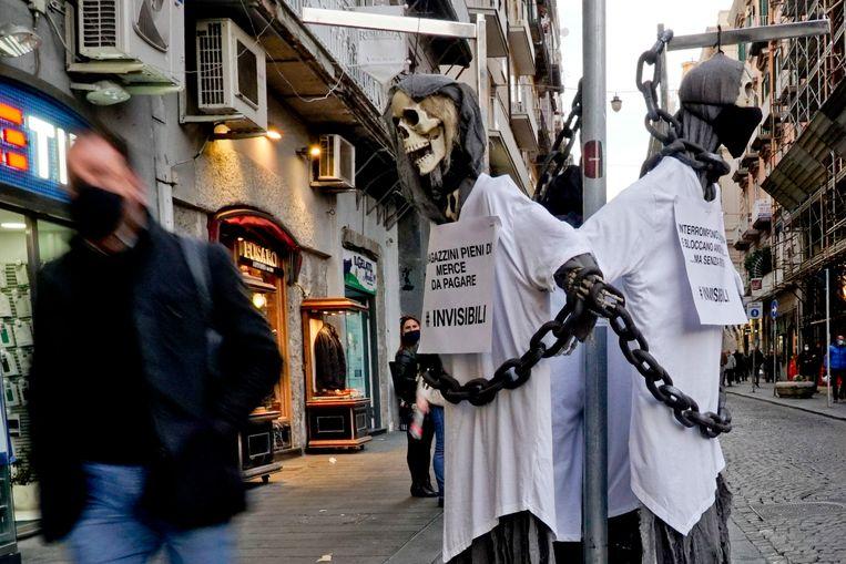 Een skelet met het opschrift 'Schande, jullie doden meer van ons dan covid' hangt in een winkelstraat in Napels. Beeld EPA