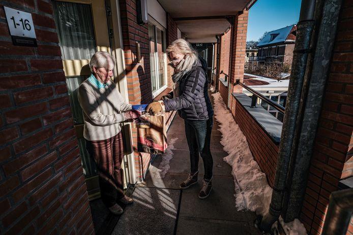 Mevrouw Worm neemt voor haar en haar man het pakket van de snertactie in ontvangst.
