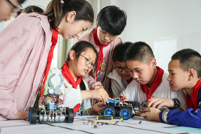 Chinese basisschoolleerlingen sleutelen aan een robotauto.  Beeld Barcroft Media via Getty Images