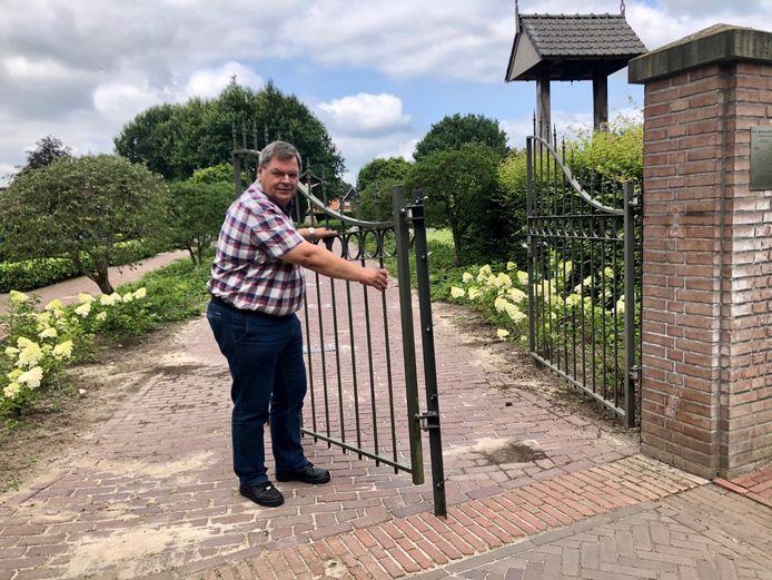 Voorzitter Alfons Steggink schudt vol onbegrip zijn hoofd als hij naar de vernielde toegangspoort van het kerkhof aan het Oldenzaalsvoetpad in Ootmarsum kijkt.