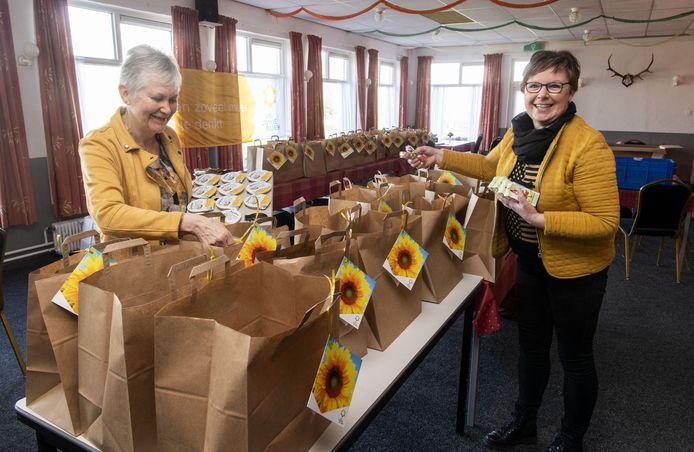 Akke Louwerman (links) en Anniek Timmers zijn twee van de vier dames die namens de lokale Zonnebloemafdeling paaspakketten samenstellen. Vooral het bezorgen kost tijd, want bij menigeen wordt aan de deur een praatje gemaakt.
