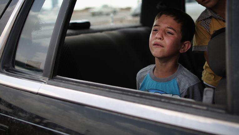Een jongetje huilt in de auto die in de rij staat bij een Koerdisch checkpoint in Kalak, Irak Beeld GETTY
