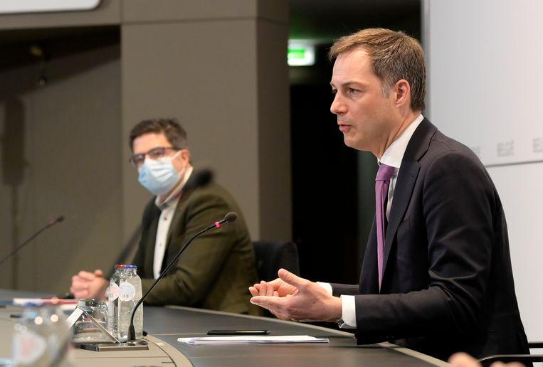 Premier De Croo, met links van hem Steven Van Gucht, op de persconferentie van maandag. Beeld BELGA