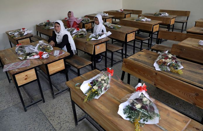 Bloemenruikers staan symbool voor de klasgenoten die omgekomen zijn bij een bomaanslag in Kaboel.