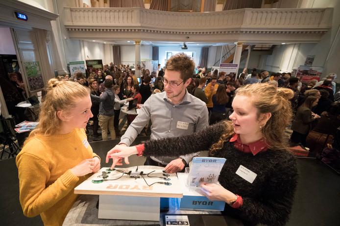 Esther Gerritsen (l) en Bo van de Groes in gesprek met Stefan van Beurden, leraar en begeleider van hun project Build Your Own Robot. Dat hebben ze samen met leerlingen van de Lambertusschool uit Haarsteeg uitgevoerd.