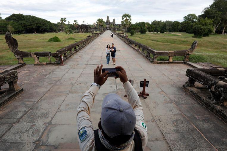Toeristen poseren voor de tempel van Angkor Wat temple in Cambodja. In normale tijden is het hier over de koppen lopen. Beeld EPA