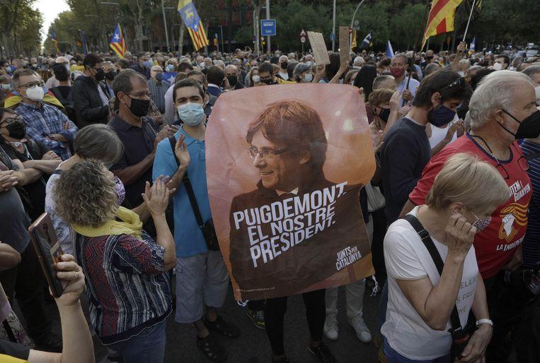 Een portret van Puigdemont met de tekst 'Puigdemont, onze president' tijdens een betoging tegen zijn arrestatie bij het Italiaanse consultaat in Barcelona. Beeld EPA