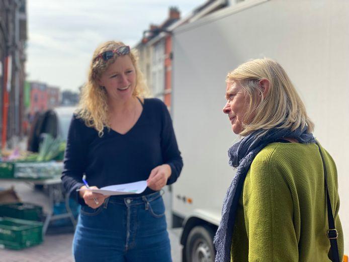 Stemmen ronselen op de Boerenmarkt van Sint-Amandsberg voor voorgestelde projecten van het Wijkbudget.