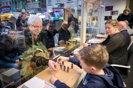 Ries, het broertje van Tijn, lakt de nagels van zijn oma bij de opening van de nagellakstudio van Serious Request op de Grote Markt in Breda. Naast hem zijn moeder. Vorig jaar begon Tijn Kolsteren uit Hapert zijn succesvolle nagellakactie bij het Glazen Huis op deze plek.  Foto: Joyce van Belkom/Pix4Profs