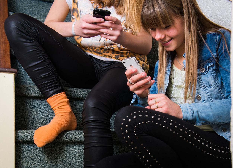 Twee meisjes spelen met hun smartphone.