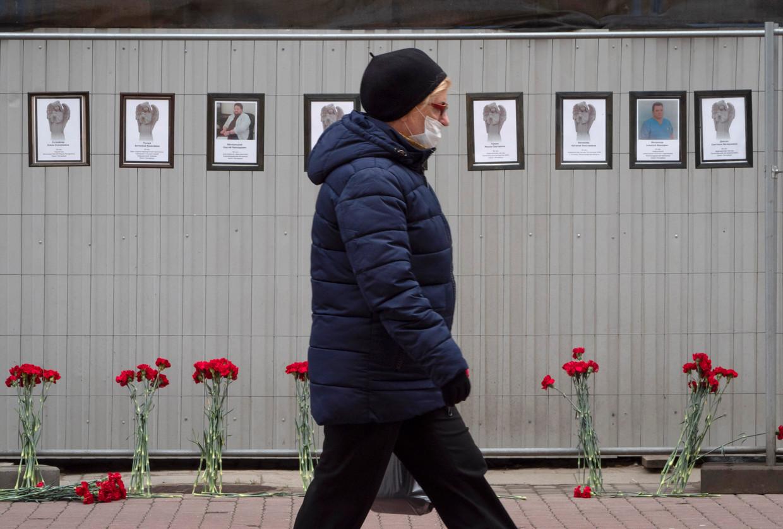 De namen en portretten van artsen die zijn omgekomen door een corona-infectie hangen op een muur in Sint-Petersburg.  Beeld AP