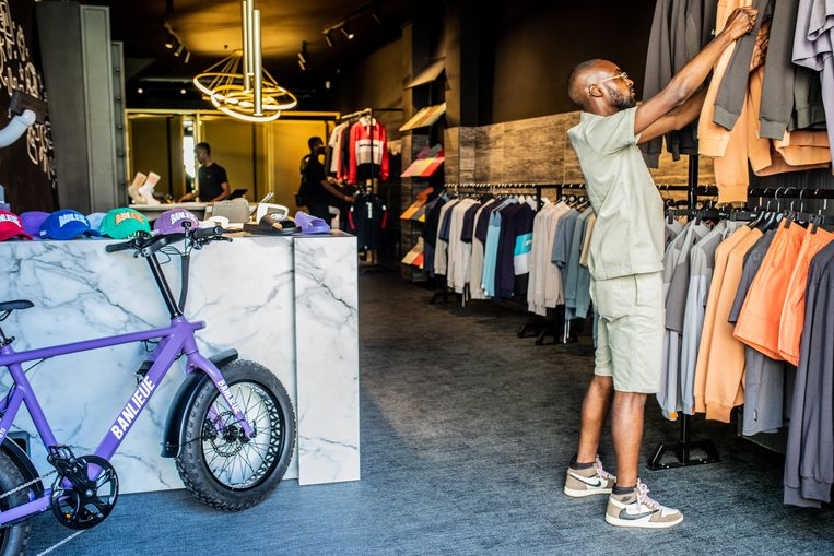 De winkel hangt vol met uniseks truien, shirts en trainingspakken.  Beeld Nosh Neneh