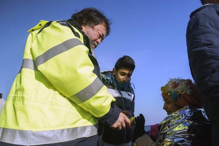 Ai Weiwei op een strand in Lesbos met twee vluchtelingen. Beeld ap